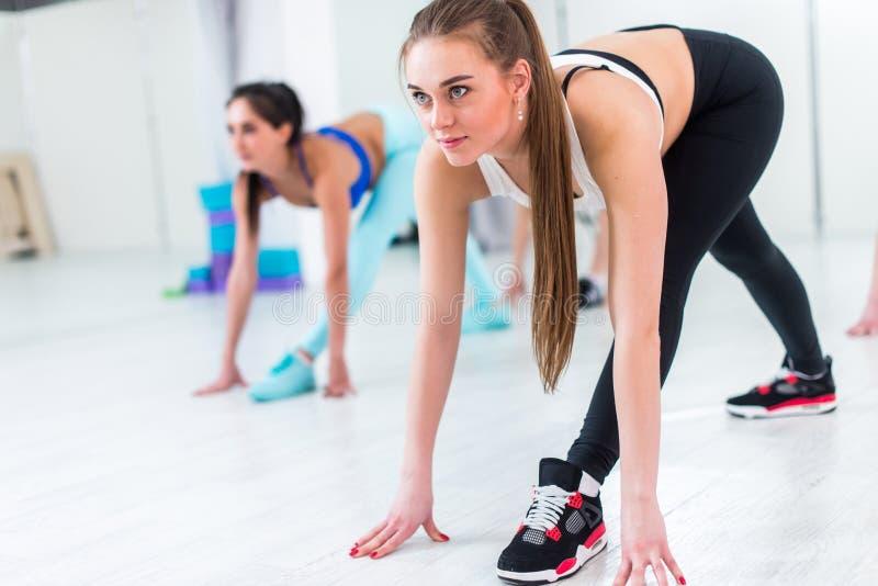Bärande sportsweardeltagande för nätt slank flicka i gruppkonditiongrupper som sträcker henne ben och baksida, genom att göra krö arkivfoton