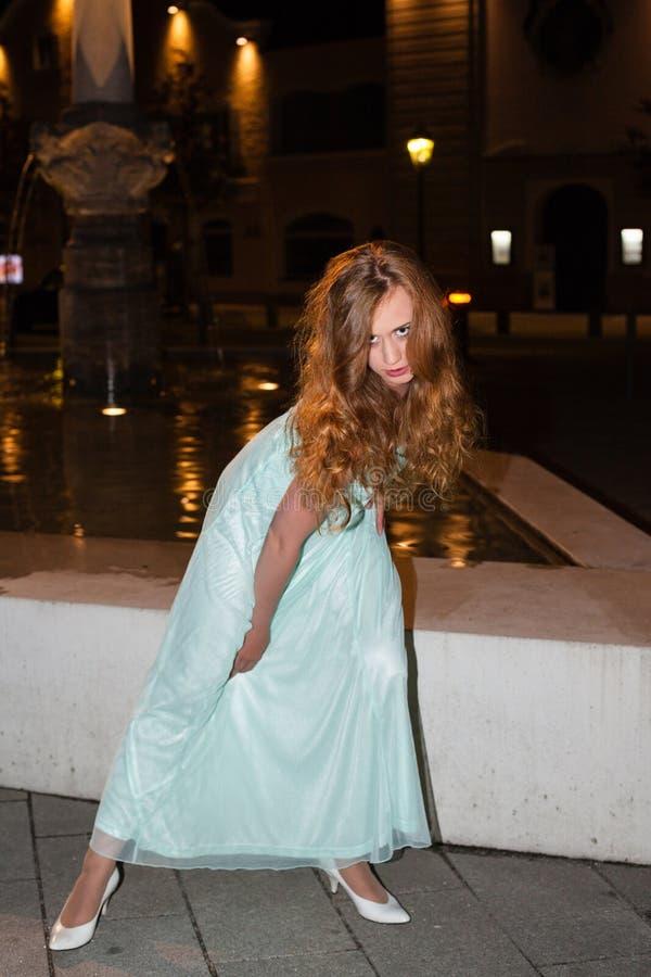 Bärande studentbalklänning för ung kvinna utomhus på natten fotografering för bildbyråer