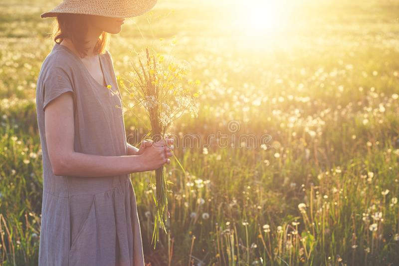 Bärande sugrörhatt för härlig kvinna och lång linneklänning som tycker om naturen som rymmer buketten av nya härliga vildblommor  royaltyfri fotografi