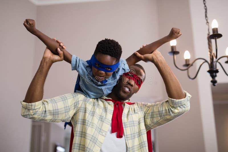 Bärande superherodräkt för fader och för son hemma arkivfoton