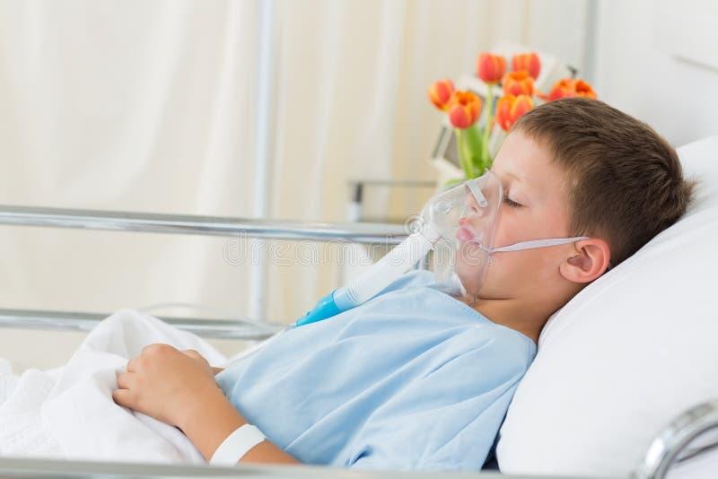 Bärande syremaskering för sjuk pojke i sjukhus arkivbild