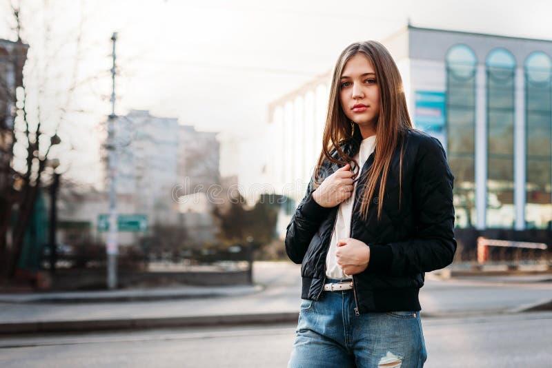 Bärande t-skjorta för flicka och läderomslag som poserar mot gatan, stads- bekläda stil royaltyfri bild