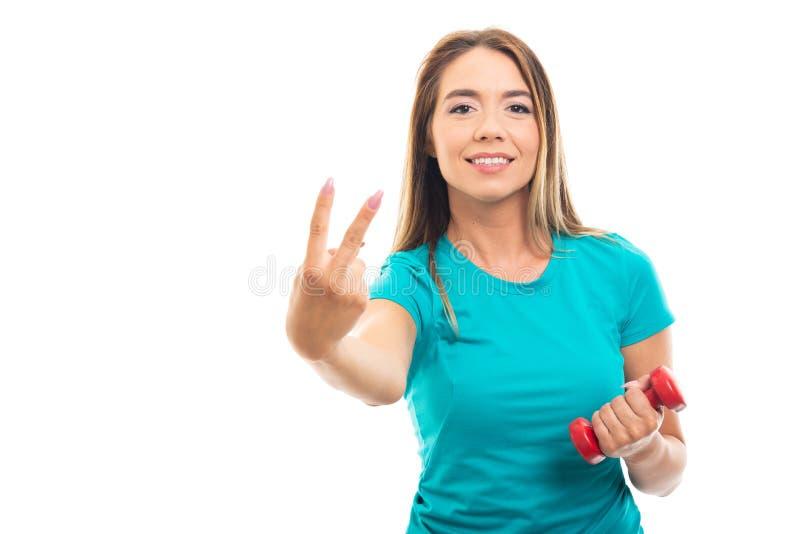 Bärande t-skjorta för ung nätt flicka visning nummer två med fingret arkivbild