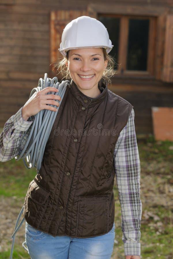 Bärande trådar för lycklig kvinnlig byggnadsarbetare fotografering för bildbyråer