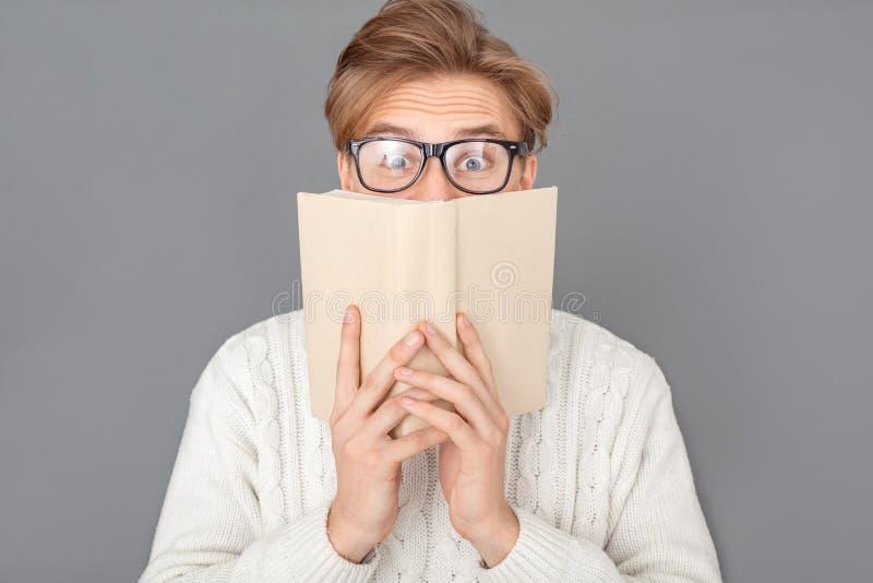 Bärande tröja för ung man och exponeringsglasstudio som isoleras på grått nederlag bak boken arkivfoto
