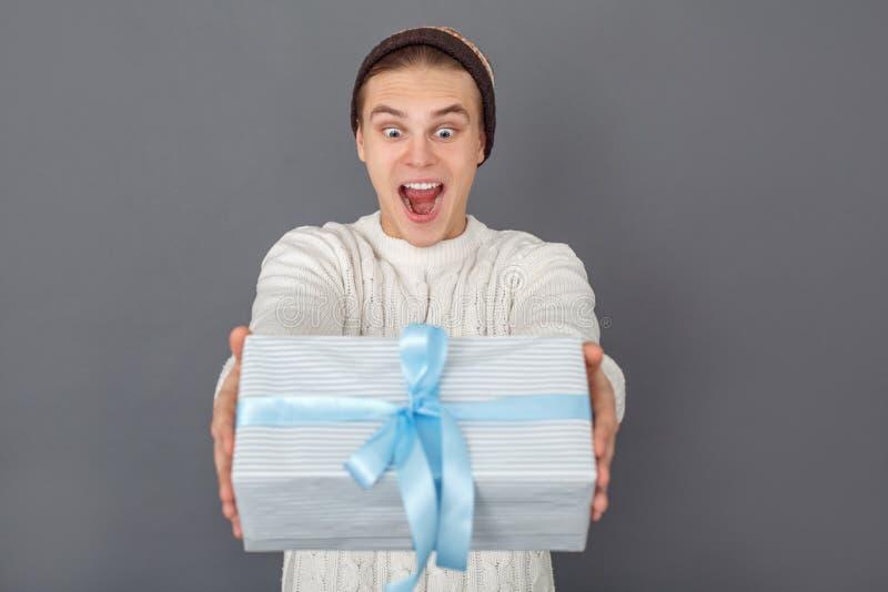 Bärande tröjastudio för ung man som isoleras på den förvånade gråa hållande gåvan arkivfoton