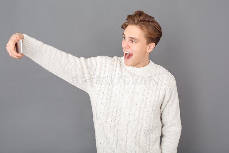 Bärande tröjastudio för ung man som isoleras på grå färger som tar glade selfiefoto arkivbild