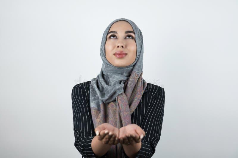 Bärande turbanhijab för ung härlig hoppfull muslimsk kvinna, sjalett som rymmer hennes händer som ser tillsammans upp isolerade royaltyfria bilder