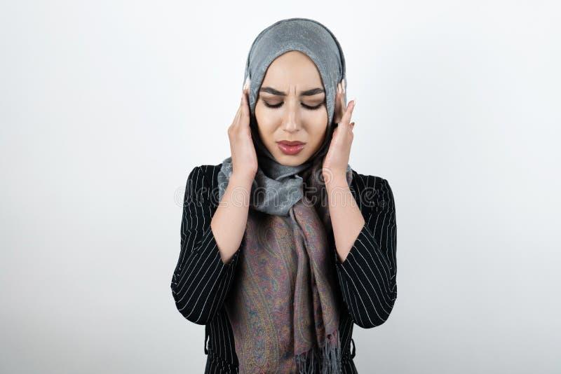 Bärande turbanhijab för ung härlig irriterad muslimsk kvinna, sjalett som ser ilsken med hennes händer som stänger öron fotografering för bildbyråer