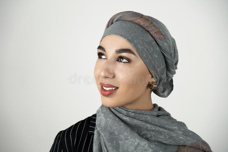 Bärande turbanhijab för ung härlig muslimsk kvinna, sjalett som ser lycklig vit bakgrund royaltyfri bild