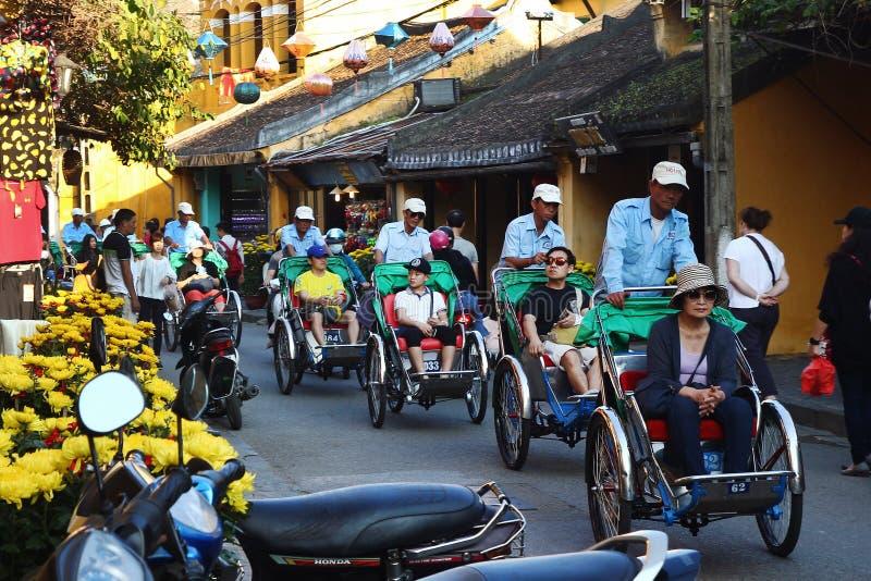 Bärande turister för Cyclo traditionell rickshaw på en gata av den historiska mitten i gammal stad arkivbilder