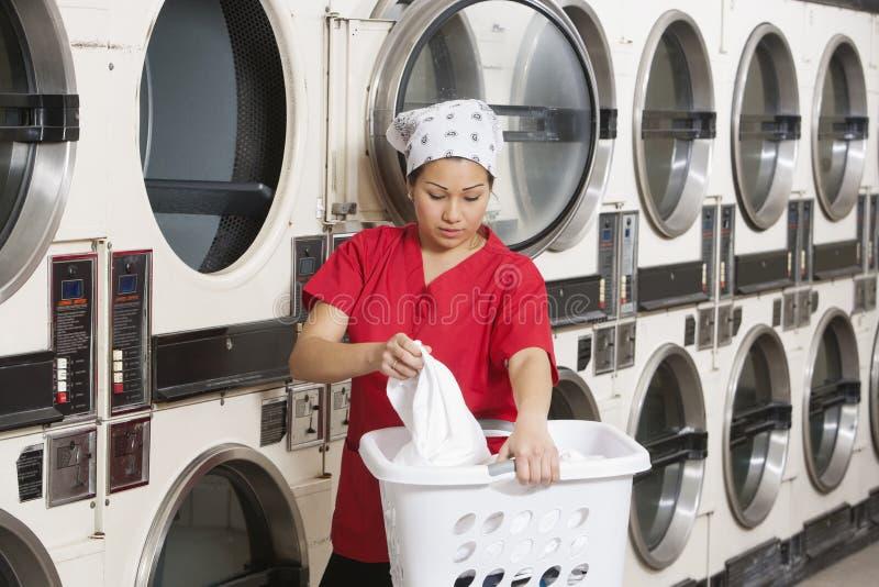 Bärande tvättkorg för ung kvinnlig anställd med tvagningmaskiner i bakgrund arkivfoto
