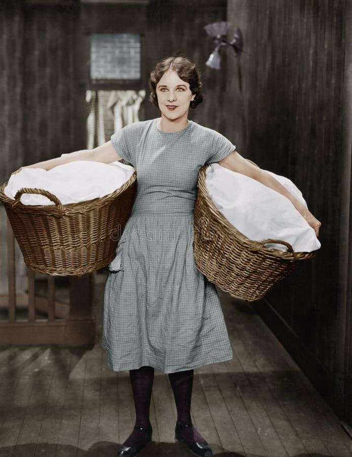 Bärande tvättkorgar för kvinna royaltyfri fotografi