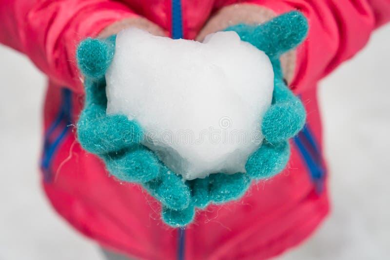 Bärande vinterhandskar för barn som rymmer iskall snöhjärta royaltyfria foton