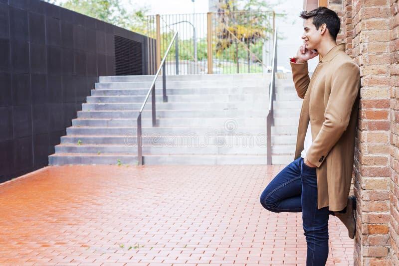 Bärande vinterkläder för ung man i gatan genom att använda hans telefon Ung grabb med den moderna frisyren med laget, jeans och t royaltyfri bild