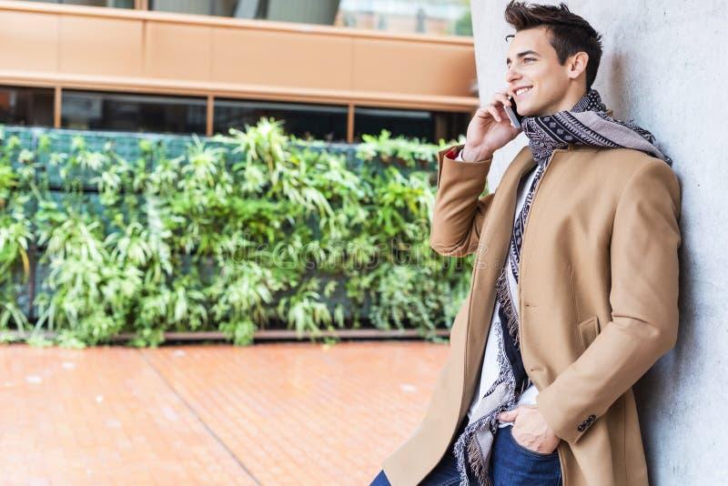 Bärande vinterkläder för ung man i gatan genom att använda hans telefon Ung grabb med den moderna frisyren med laget, jeans och t arkivbild