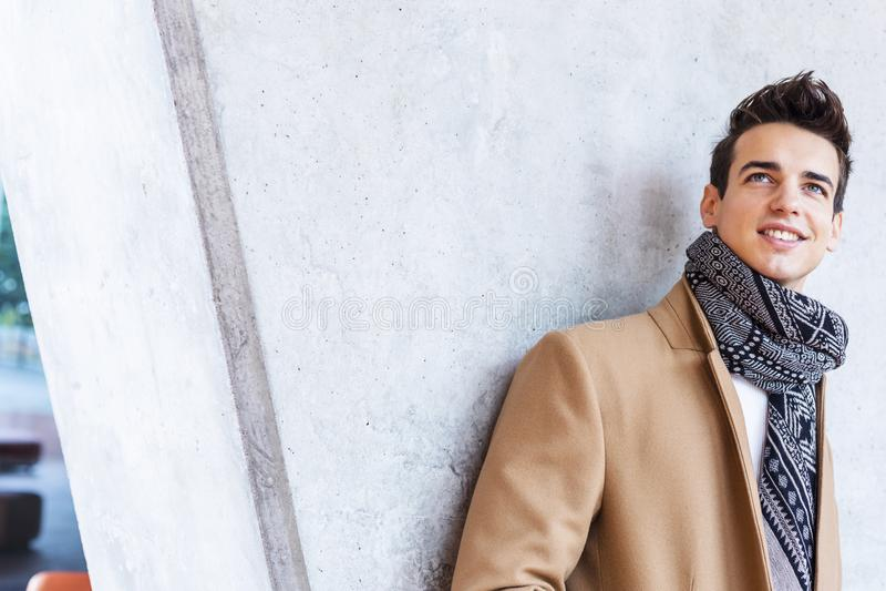 Bärande vinterkläder för ung man i gatan Ung grabb med den moderna frisyren med laget, jeans, halsduken och vit mer sweeter arkivfoton