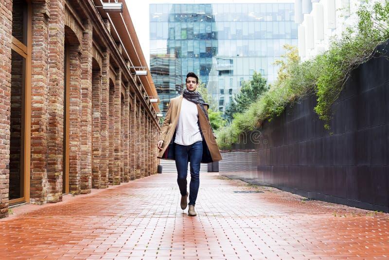 Bärande vinterkläder för ung man i gatan Ung grabb med den moderna frisyren med laget, jeans och vit mer sweeter fotografering för bildbyråer