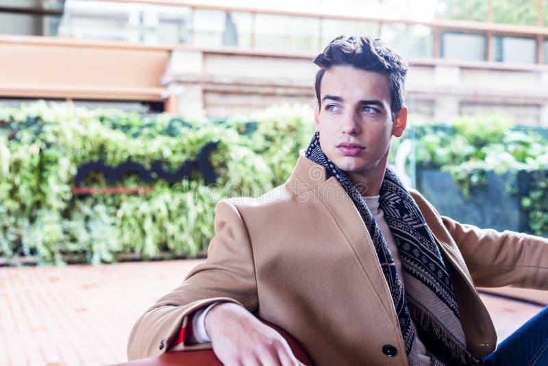 Bärande vinterkläder för ung man i gatan Ung grabb med den moderna frisyren med laget, jeans och vit mer sweeter royaltyfri foto