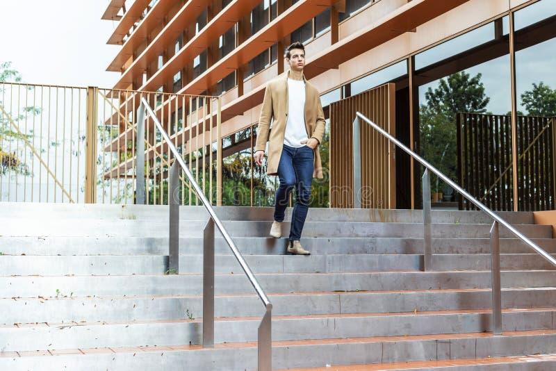 Bärande vinterkläder för ung man i gatan Ung grabb med den moderna frisyren med laget, jeans och vit mer sweeter royaltyfri bild