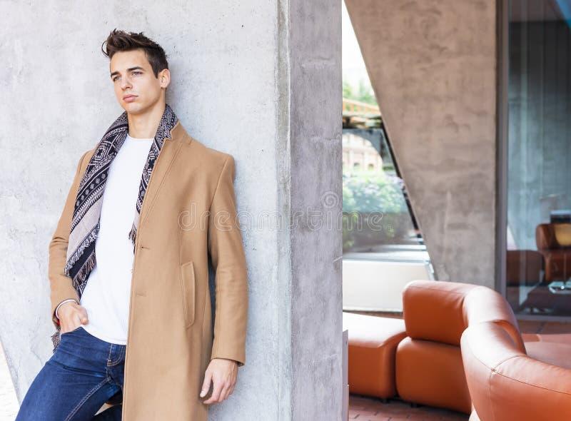 Bärande vinterkläder för ung man i gatan Ung grabb med den moderna frisyren med laget, jeans och vit mer sweeter royaltyfri fotografi