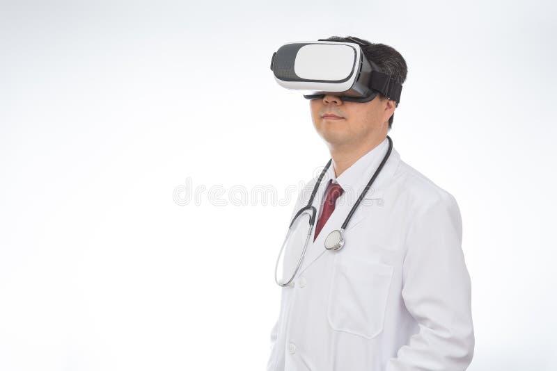 Bärande virtuell verklighetexponeringsglas för manlig doktor som isoleras på vit bakgrund arkivfoto