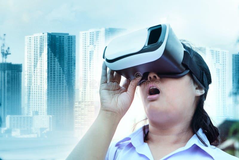 Bärande virtuell verklighetexponeringsglas för mer ung kvinna med att förvåna framsidaanseendet som är utomhus- mot modern stadsb arkivfoto