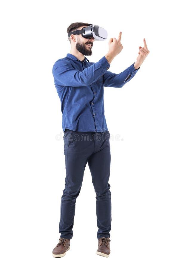 Bärande virtuell verklighetexponeringsglas för ohyfsad vuxen man som visar långfinger den obscna gesten som bort ser arkivbilder