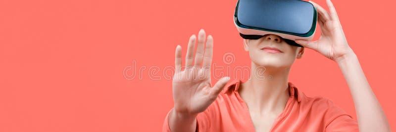 Bärande virtuell verklighetskyddsglasögon för ung kvinna Kvinna som bär VR-exponeringsglas över korallbakgrund VR-erfarenhetsbane royaltyfri fotografi