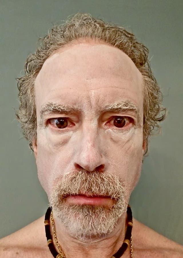 Bärande vit ansikts- Masque för äldre man arkivbilder