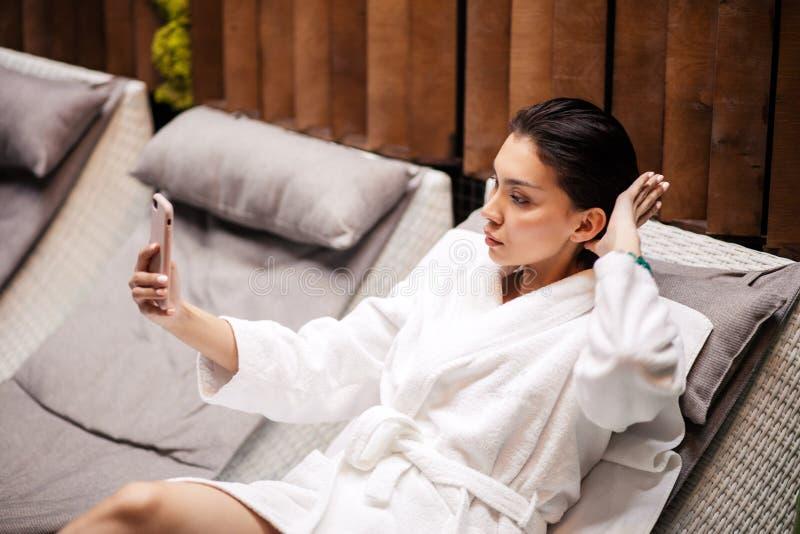 Bärande vit badrock för ung beauitiful kvinna som ligger på loungen fotografering för bildbyråer