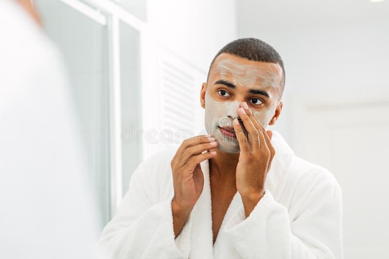Bärande vit badrock för ung man som applicerar den ansikts- maskeringen arkivfoto