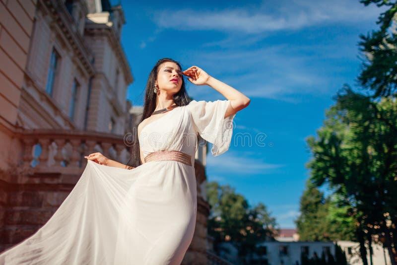 Bärande vit bröllopsklänning för härlig kvinna utomhus En skuldraklänning med tillbehör och smycken royaltyfria bilder