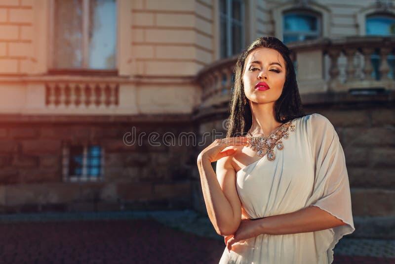 Bärande vit bröllopsklänning för härlig kvinna utomhus En skuldraklänning med tillbehör och smycken makeup arkivbild