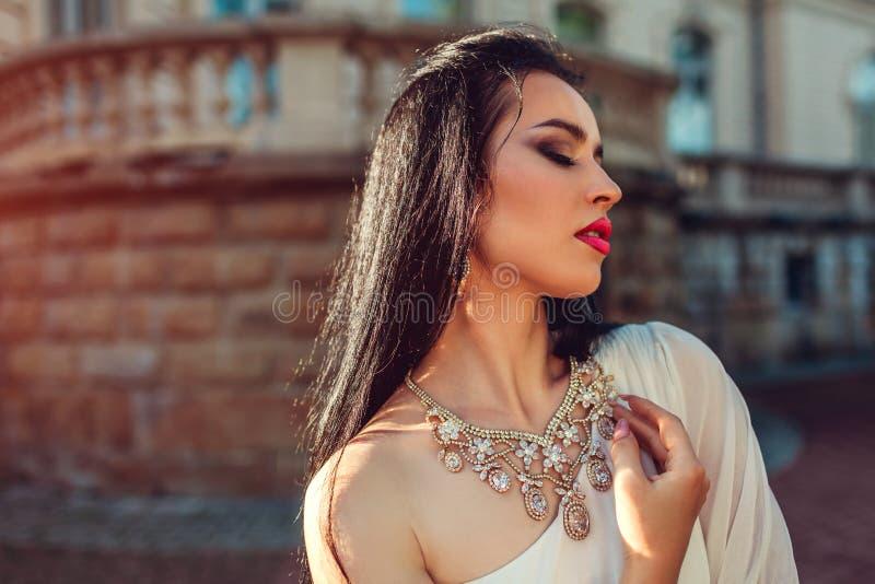Bärande vit bröllopsklänning för härlig kvinna utomhus En skuldraklänning med tillbehör och smycken makeup arkivbilder