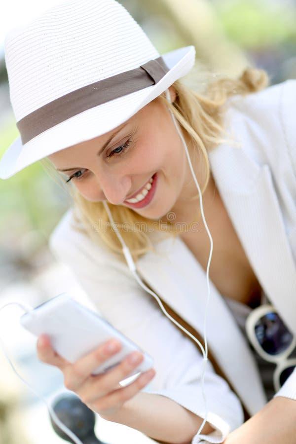 Bärande vit hatt för ung kvinna och lyssna till musik arkivbilder