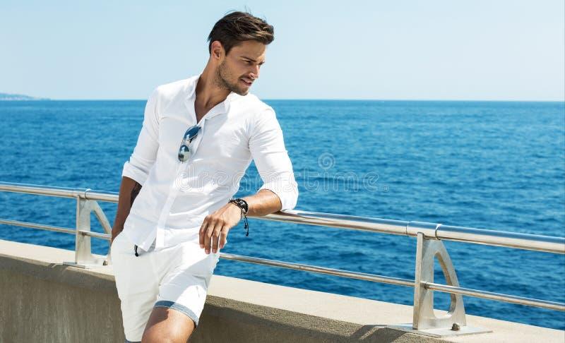 Bärande vit kläder för stilig man som poserar i havslandskap arkivbild