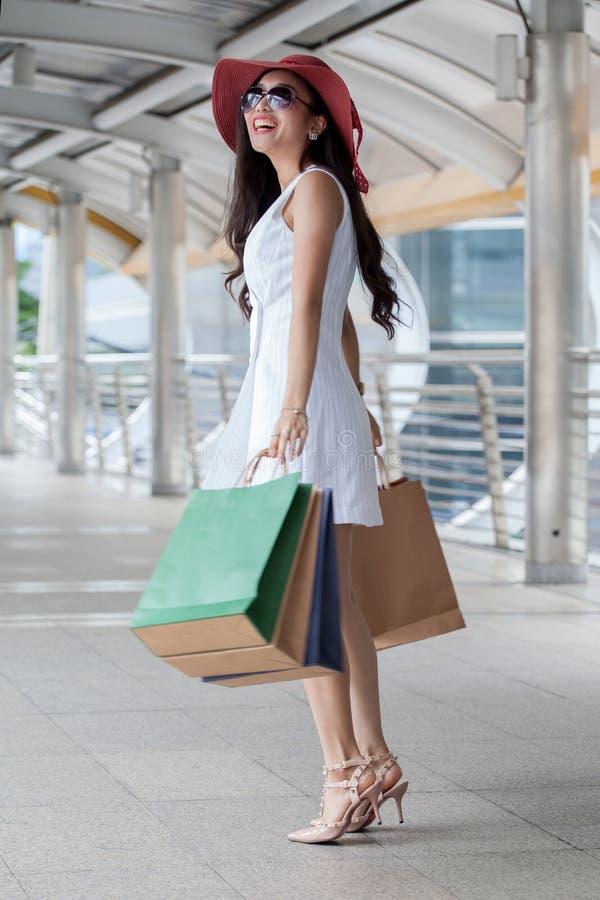 Bärande vit klänning för lycklig härlig ung asiatisk kvinna och solglasögon, röd hatt med shoppingpåsar över gallerian som in tyc royaltyfri bild