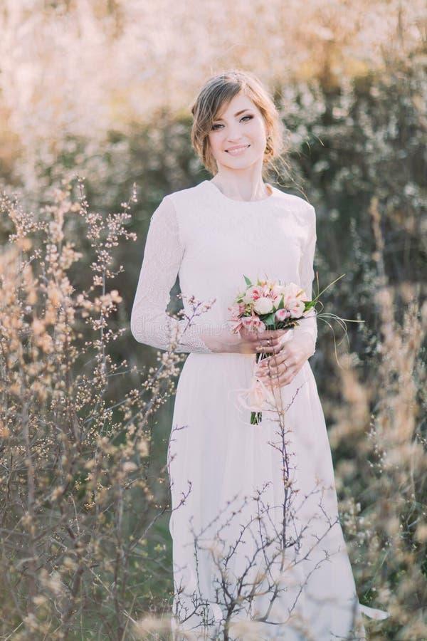Bärande vit klänning för ung härlig blond brud med buketten i blommande äng Den delikata flickan tycker om vårnaturen royaltyfri foto