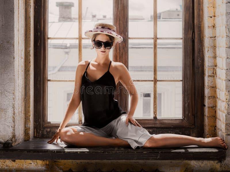 Bärande vit kortslutningar för ung kvinna, svartöverkant, hatt och solglasögon arkivfoto