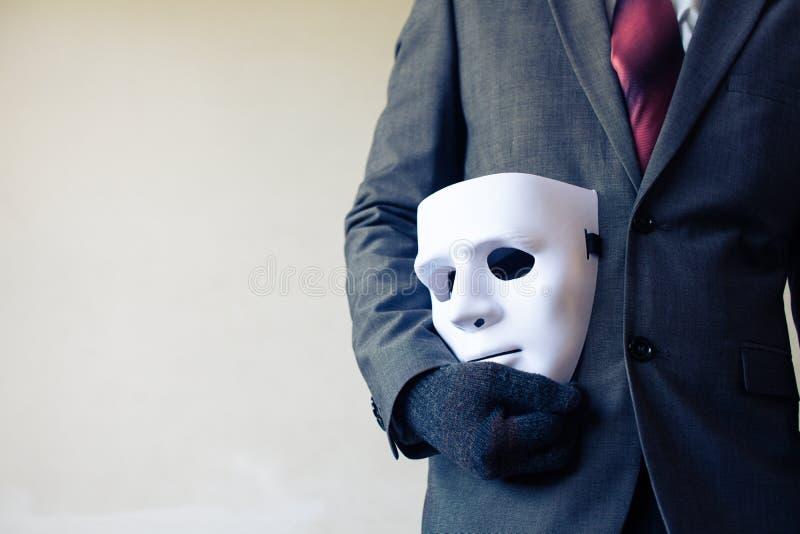 Bärande vit maskering för affärsman till hans kropp som indikerar affärsbedrägeri och fejkar affärspartnerskap royaltyfri foto