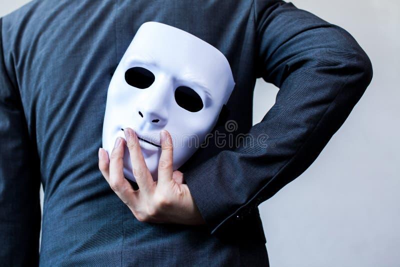 Bärande vit maskering för affärsman till hans kropp som indikerar affärsbedrägeri och fejkar affärspartnerskap fotografering för bildbyråer