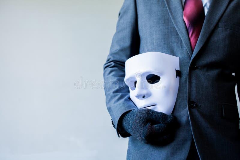 Bärande vit maskering för affärsman till hans kropp som indikerar affärsbedrägeri och fejkar affärspartnerskap royaltyfri fotografi