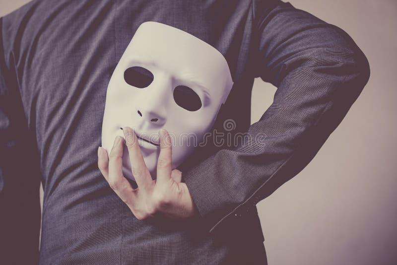 Bärande vit maskering för affärsman till hans kropp som indikerar affärsbedrägeri och fejkar affärspartnerskap royaltyfria foton