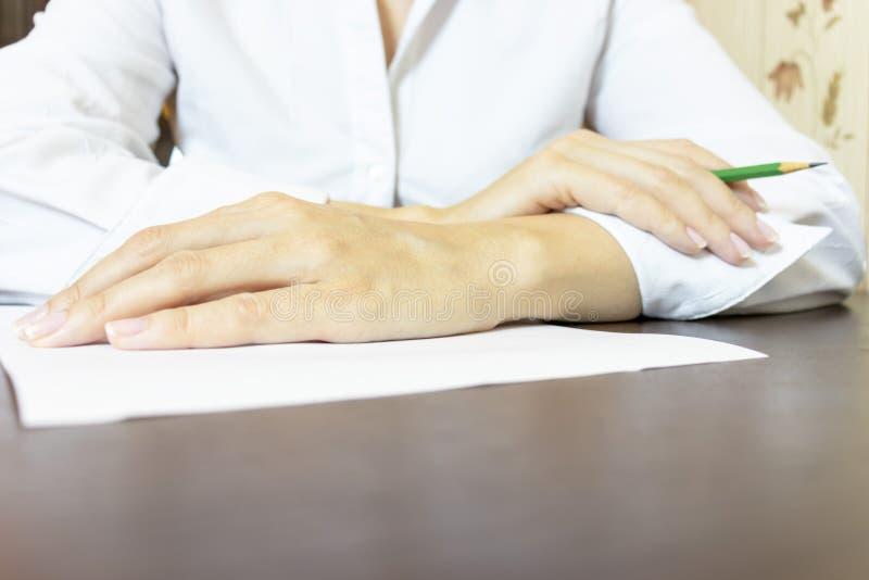Bärande vit skjorta för affärskvinna som sitter vid tabellen med ett stycke av papper och en blyertspenna arkivfoto