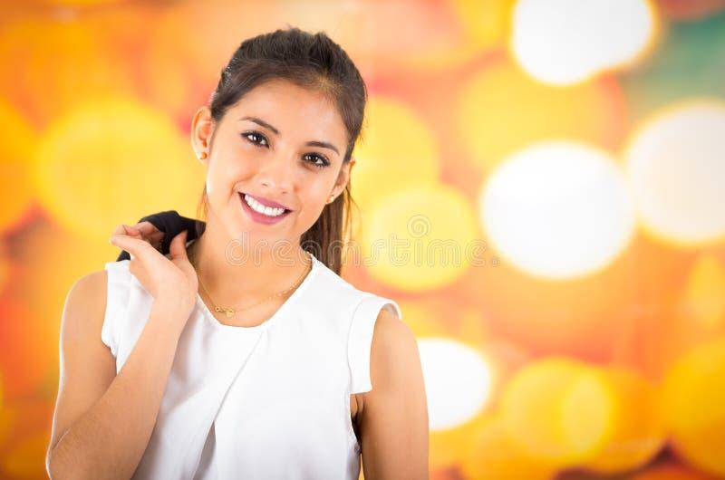 Bärande vit skjorta för attraktiv brunett som naturligt poserar och ler som är härlig till kameran med oskarp färgrik bakgrund arkivfoton