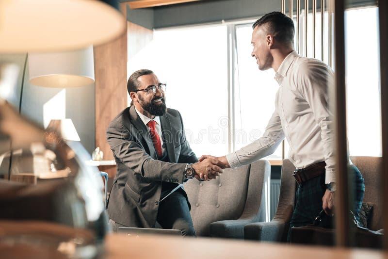 Bärande vit skjorta för ung stilig man som kommer till affärsintervjun royaltyfri bild