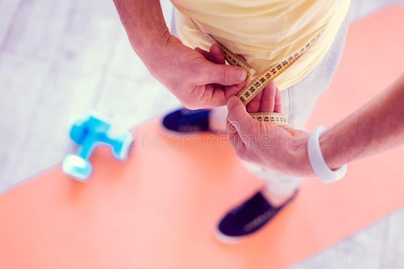 Bärande vit smart klocka för man på hans hand som mäter hans midja royaltyfria bilder