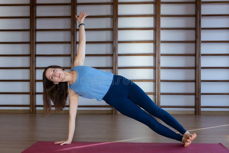 Bärande vit sportswear för ung lugna nätt kvinna som utarbetar och att göra yoga- eller pilatesövning Full längd arkivfoto