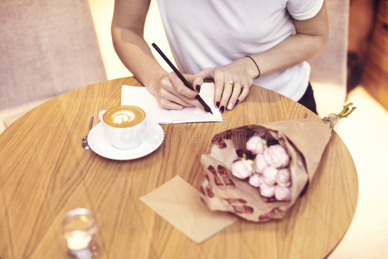 Bärande vit t-skjorta för närbildhipsteraffärskvinna handstil i kafé på startup projekt royaltyfri bild